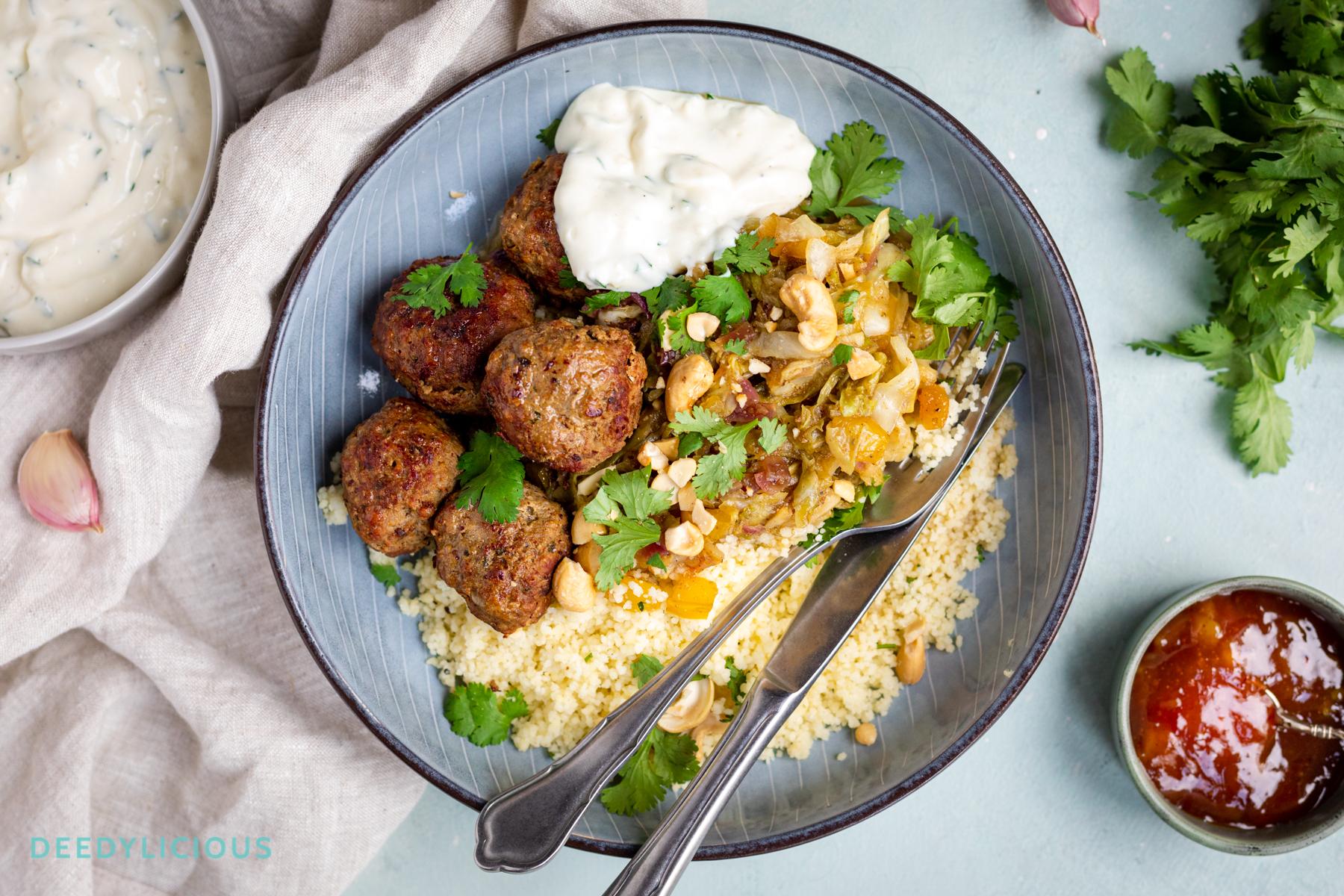 Bovenaanzicht van een bord met daarop couscous, gehaktballen en zelfgemaakte knoflooksaus