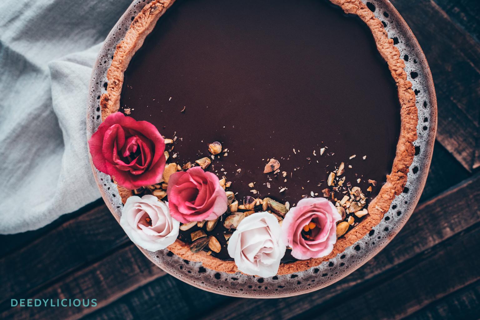 Italiaanse chocoladetaart versierd met bloemen en pistachenoten