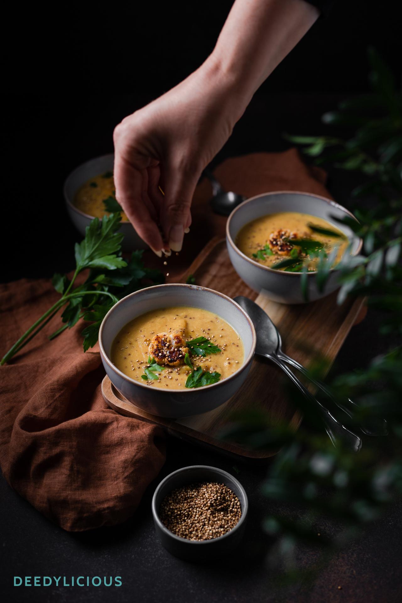 Hand strooit gepofte quinoa in kommetje bloemkoolsoep.
