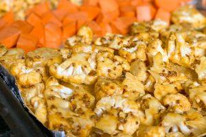 Ovenplaat met bloemkoolroosjes en zoete aardappelblokjes