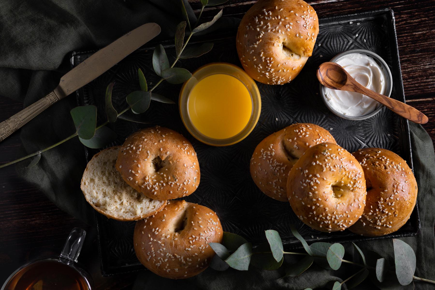 Schaal met vers gebakken bagels, vers geperst sinaasappelsap en een bakje Cream cheese