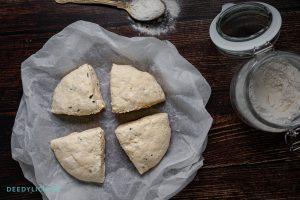 Deeg voor bagels verdeeld in 4 gelijke stukken op een houten ondergrond.
