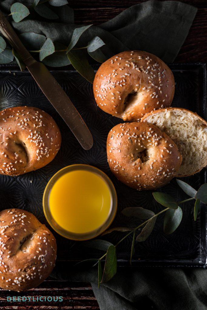 Schaal met vers gebakken bagels, met vers geperst sinaasappelsap