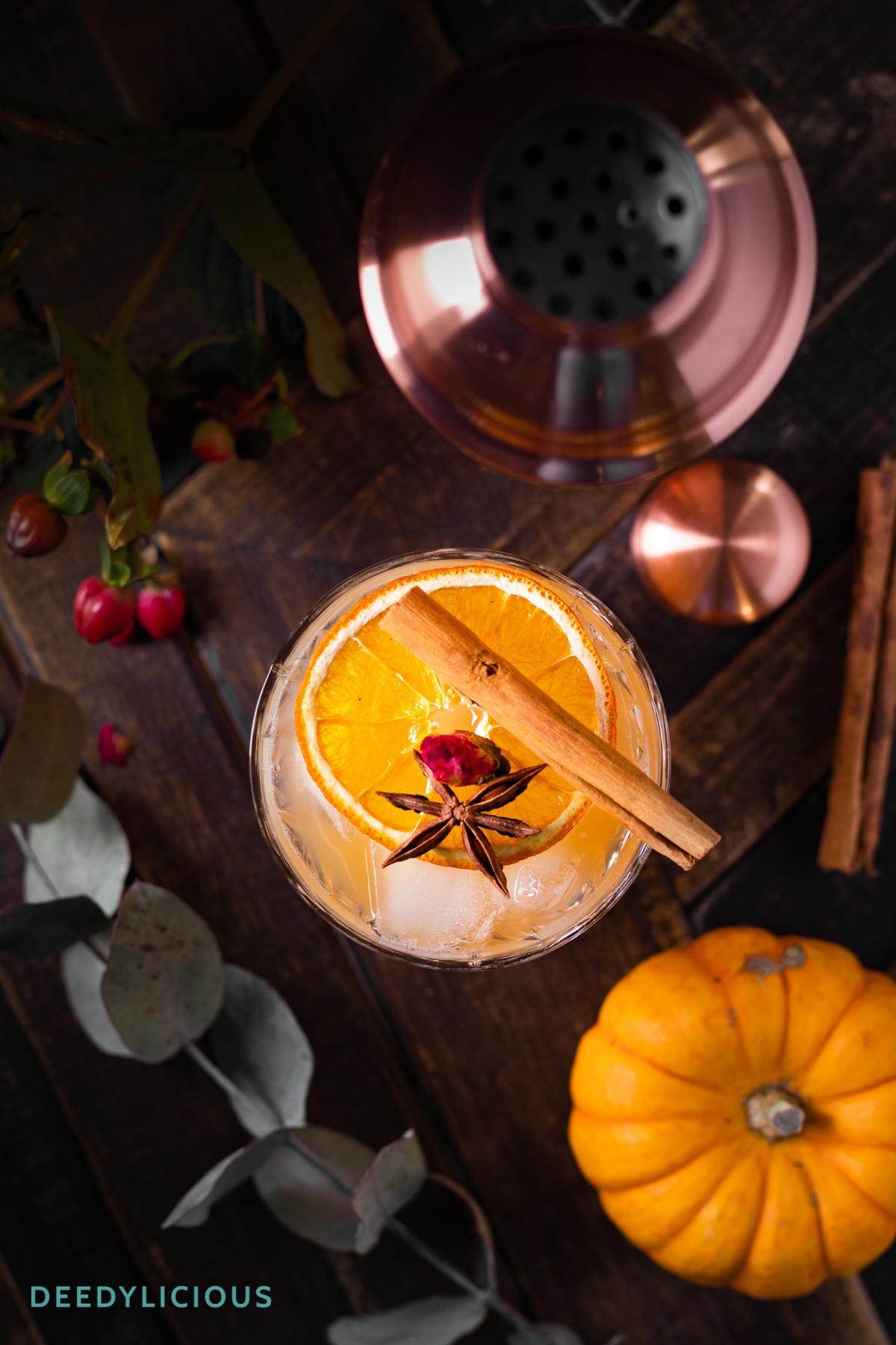 Glas met kruidige cocktail met kaneelstokje van bovenaf gefotografeerd, met shaker in achtergrond
