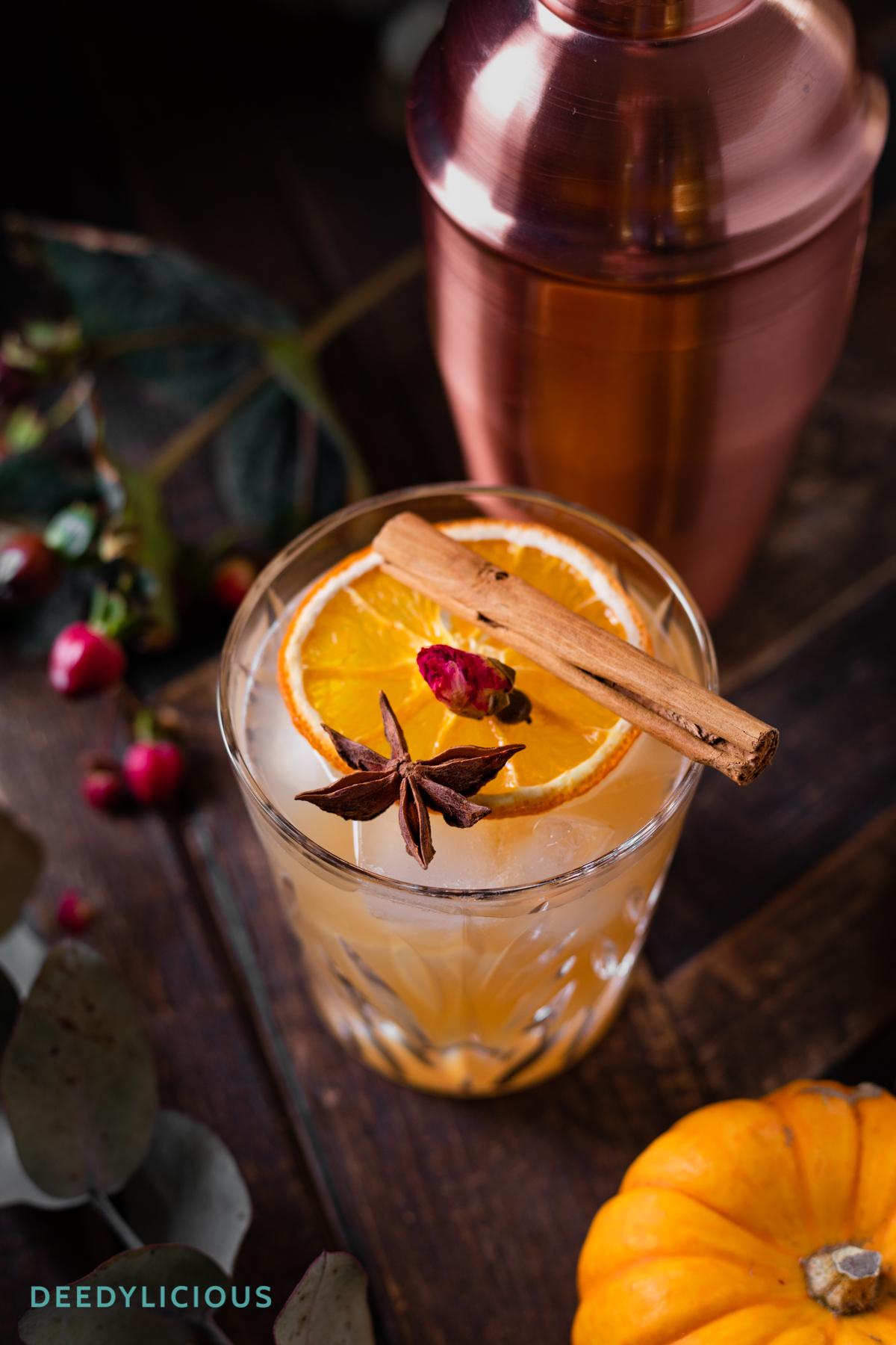 Glas met kruidige cocktail met kaneelstokje bovenop met shaker en takken in achtergrond