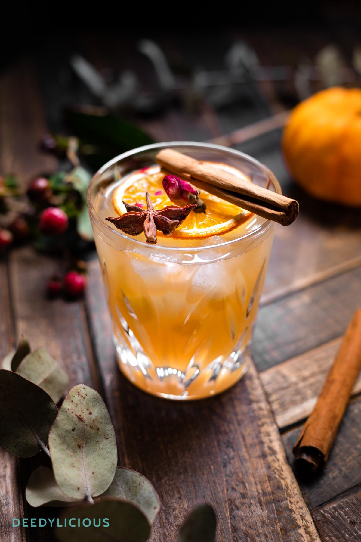 Glas met kruidige cocktail met kaneelstokje bovenop | Food fotograaf DeedyLicious