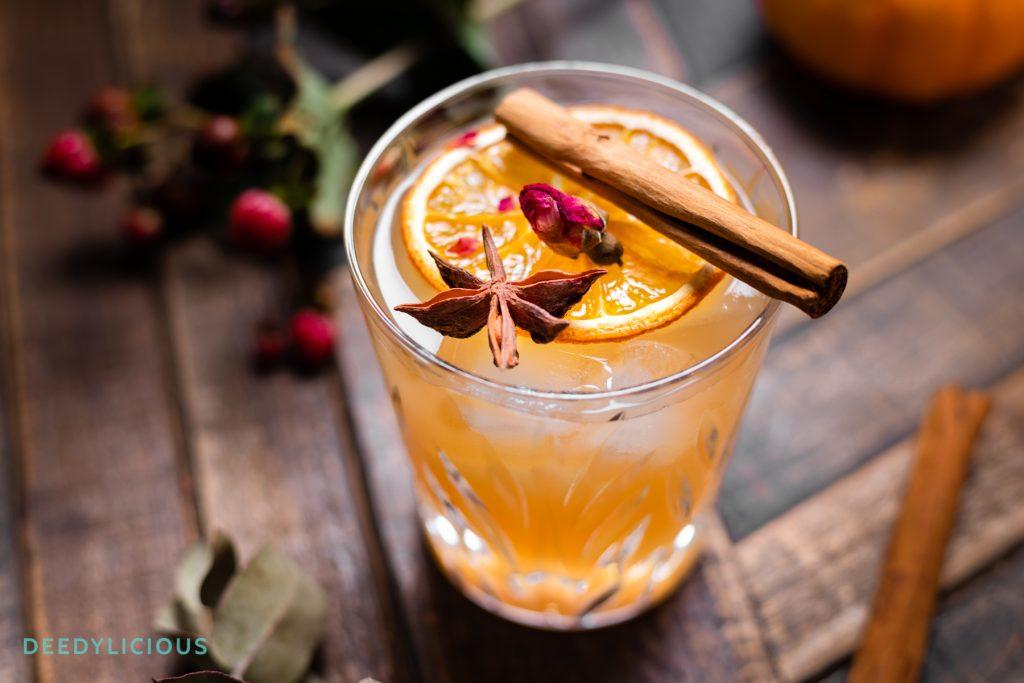 Glas met kruidige cocktail met kaneelstokje bovenop