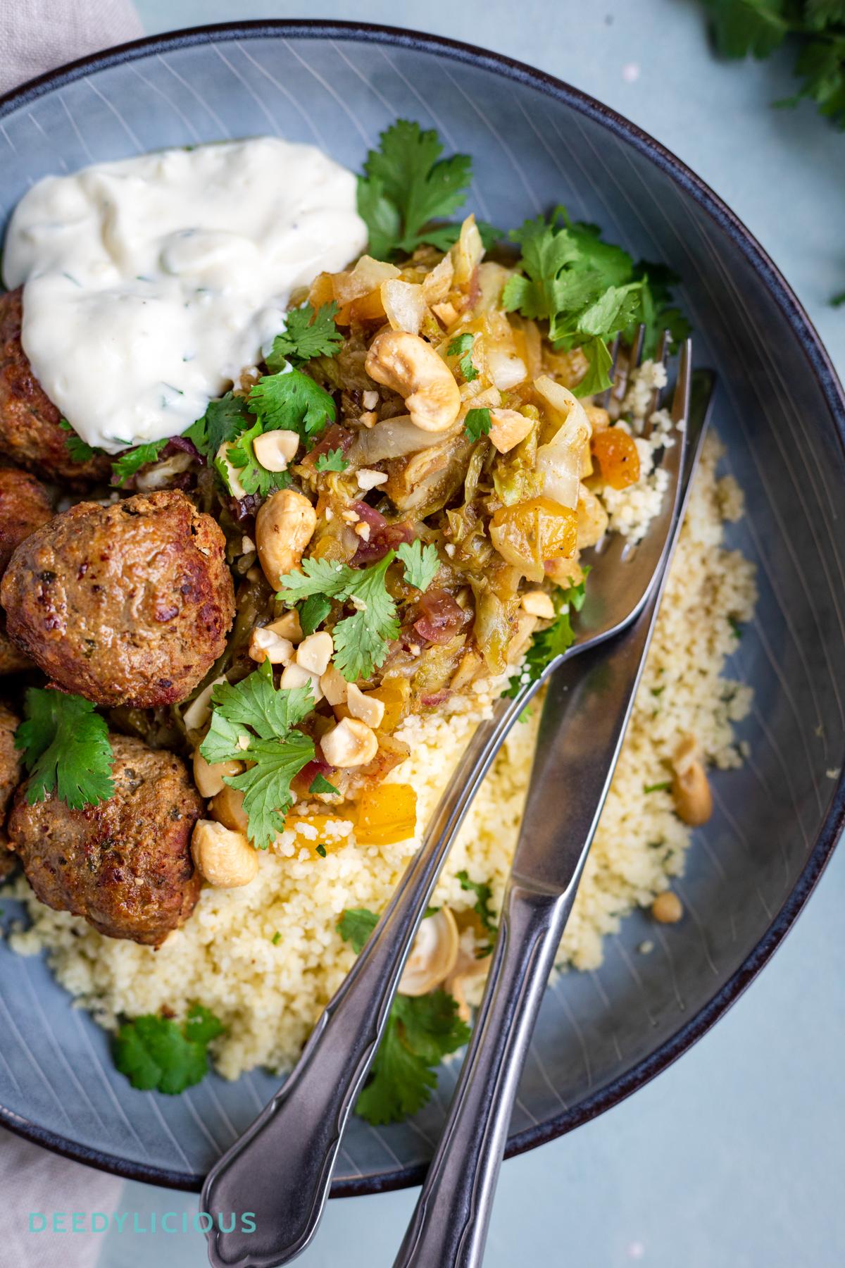 Detail van een bord met Mango couscous met pittige gehaktballen en zelfgemaakte knoflooksaus