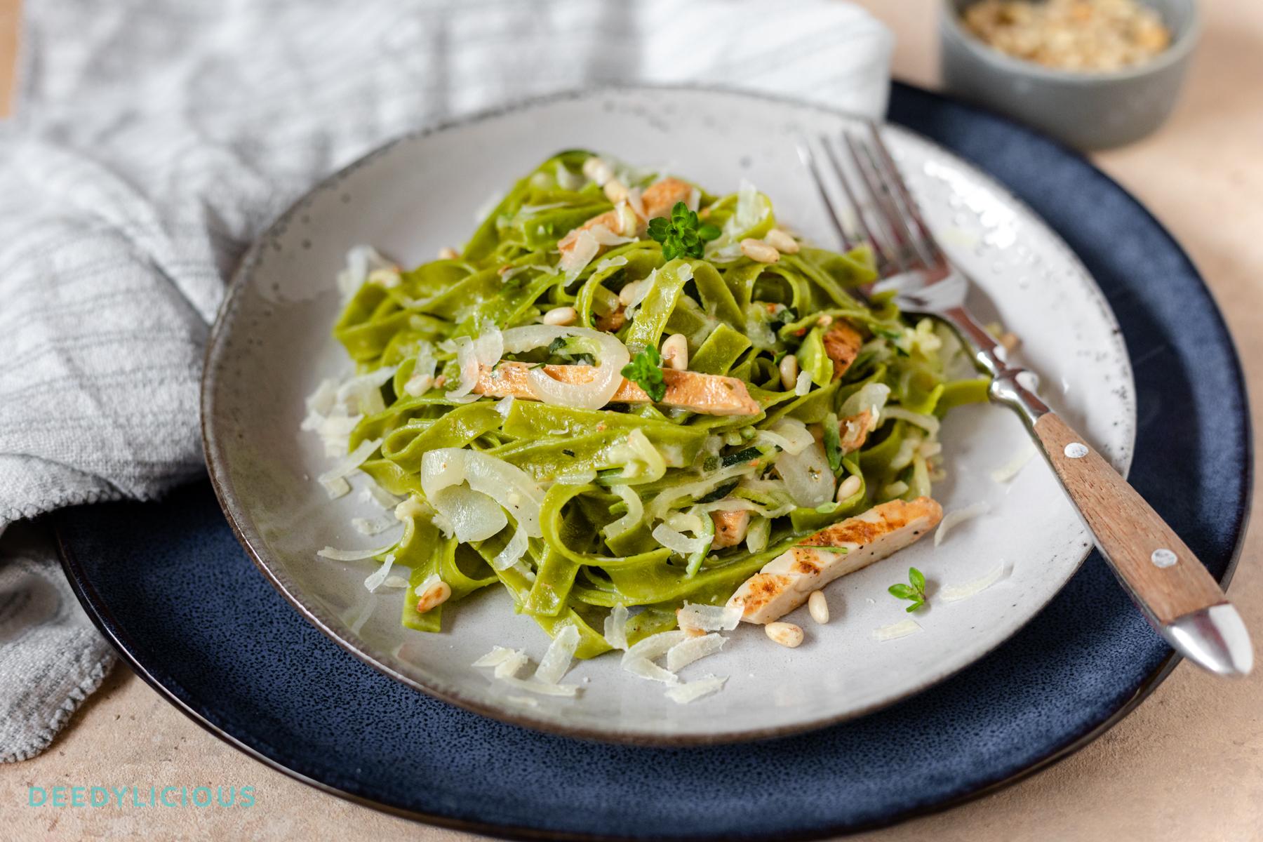 Groene Tagliatelle met courgetti, gebraden kip en kaassaus op een bord