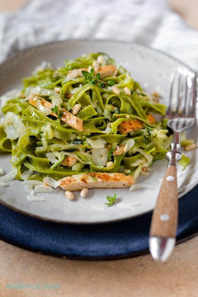 Een bord met de groene Tagliatelle met courgetti, gebraden kip en kaassaus op een bord