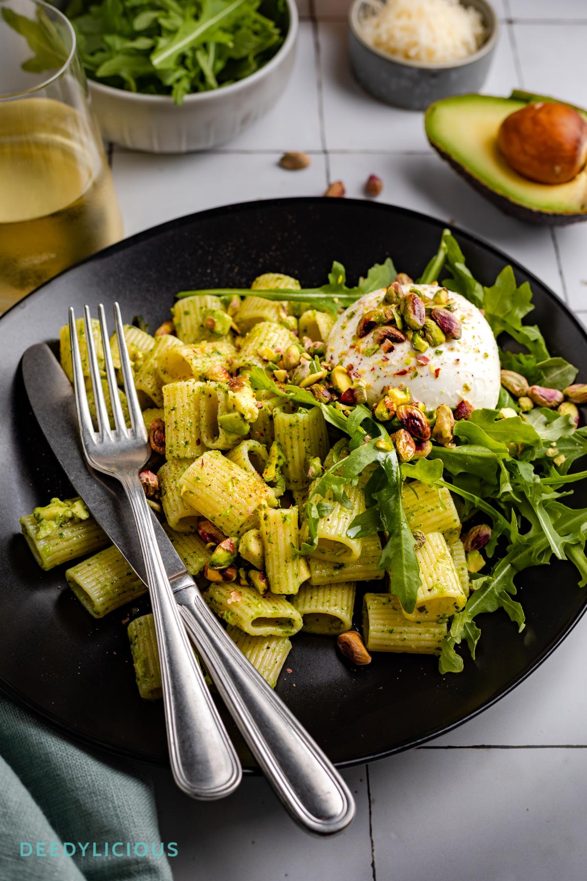 Rigatoni pasta met pesto, pistache en avocado, geserveerd op een zwart bord met witte tegels op de ondergrond